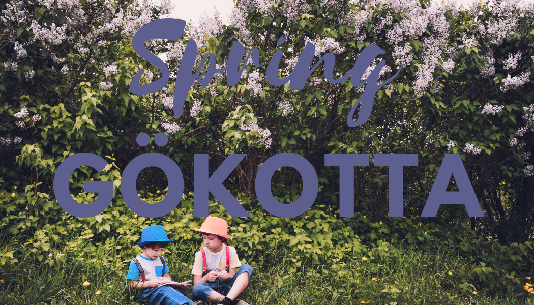 1,000 Hours outside: spring Gokotta image of tow children sitting outside in front of flower bushes.
