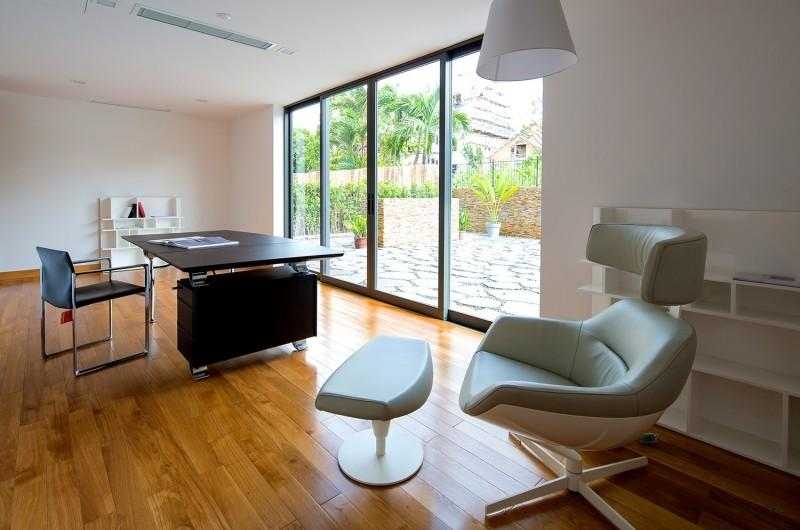 Trip to Thao Dien Vietnam and Take Ultra-Modern Fuschia Villa: charming white sofa bed plus wooden office desk feat blue chair on laminate floor paired with white pendant lamp also glass wall