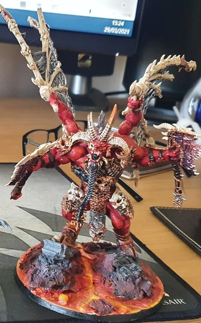 Skarbrand, painted with red skin and bone wings.  He is mounted on rocks over a lava stream.