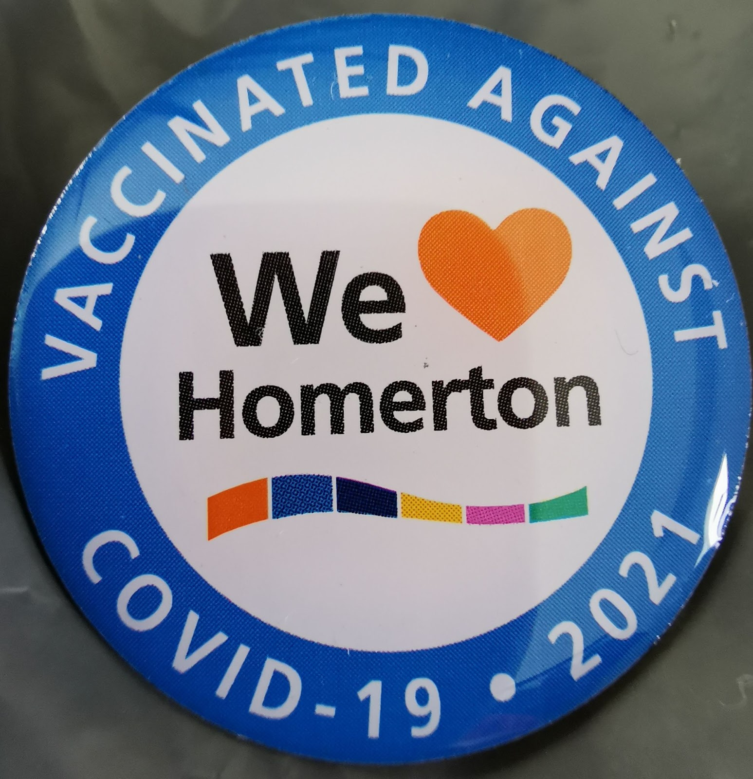 "image of a badge from Homerton hospital which states ""vaccinated against covid 19 2021"" around the edge and ""we love Homerton"" in the centre"