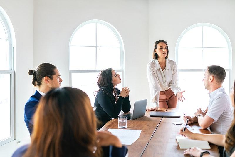 Uma mulher falando algo no escritório para outras pessoas.