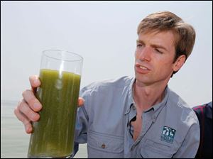 Man holds glass of polluted water from river.
