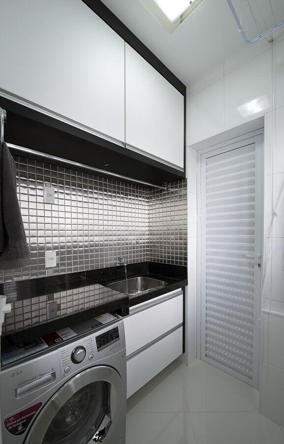 Lavanderia com pastilhas metalizadas na cor preta, pia e bancada de mármore preto, lavadora de inox e piso porcelanato branco.