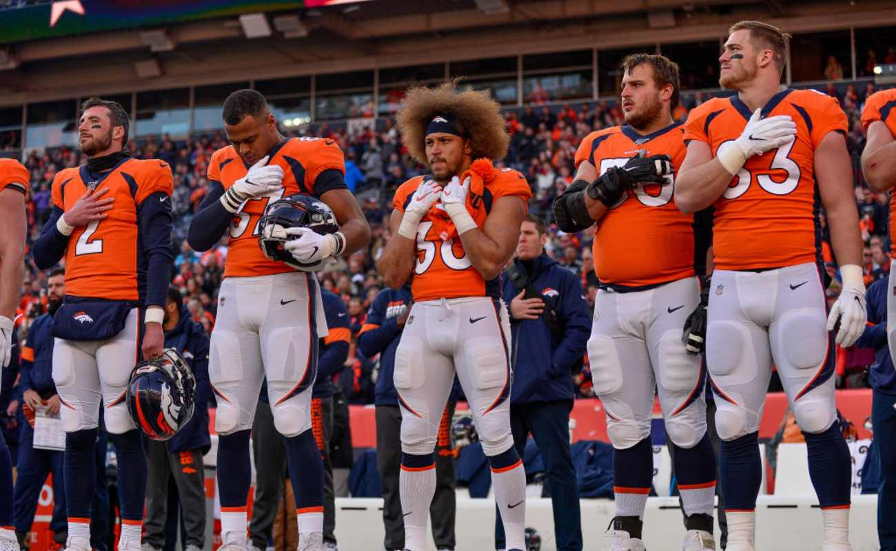 Denver Broncos players stand on the field during the performance of the national anthem before a game against the Oakland Raiders December, 2019
