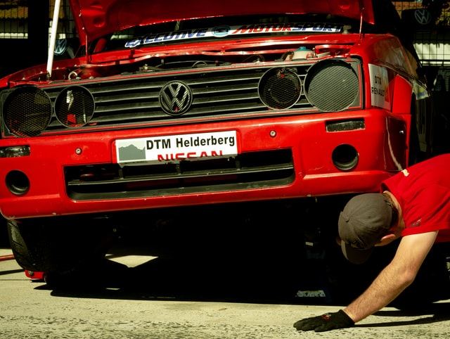 man looking underneath and inspecting the vehicle