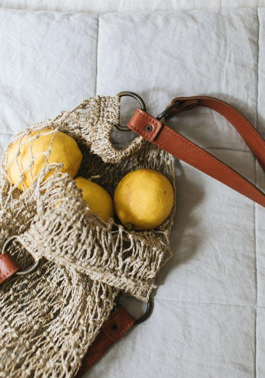 From above of delicious fresh quinces in ecological bag with leather strap on crumpled duvet