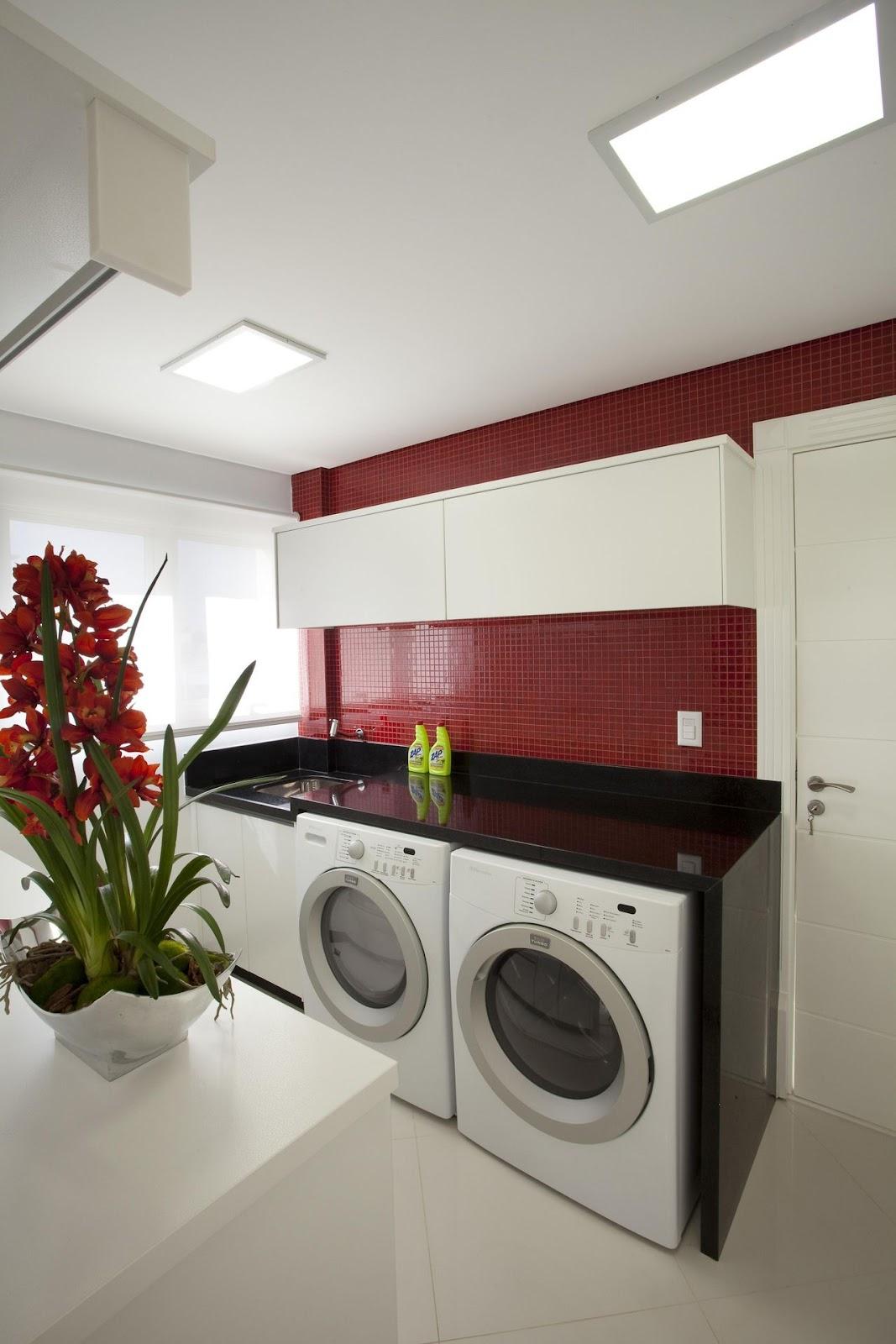Imagem de uma área de serviços pequena, contendo uma pia, duas máquinas de lavar. O destaque se dá pela presença de azulejos vermelhos, valorizando o ambiente.