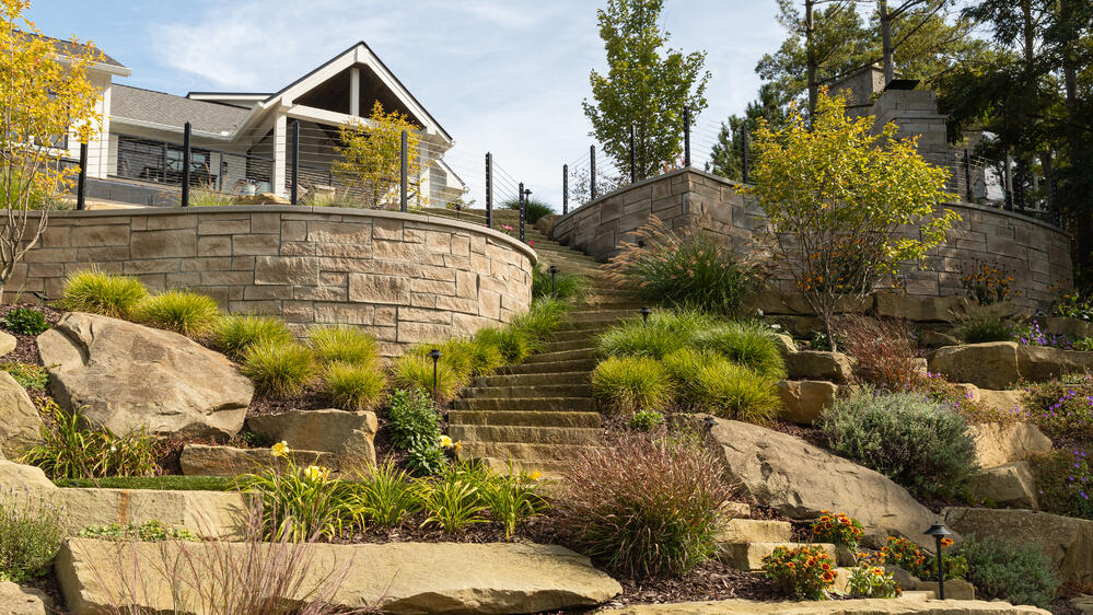 Indiana Limestone garden steps harmoniously blend with the natural look of the sandstone boulders and rustic Berkshire™ veneer.