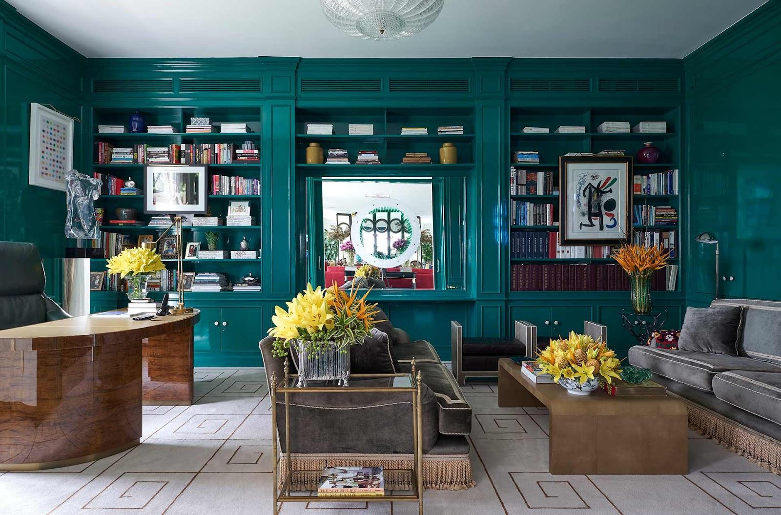 Escritório com armário verde, sofás, e mesas com plantas.