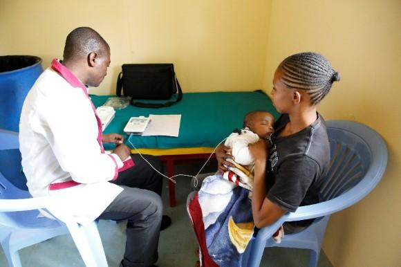 Doctor with mother and baby performing a sensory test