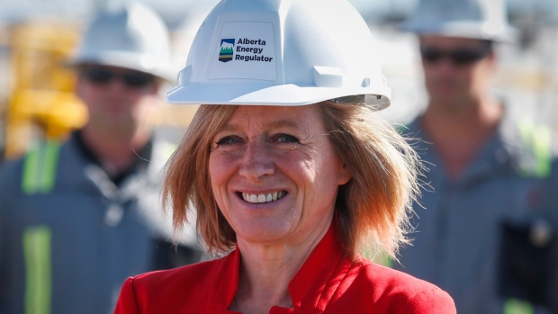 Alberta Premier Rachel Notley waits before making an announcement regarding work to speed the cleanup of Alberta's old energy infrastructure near Carstairs, Alta.