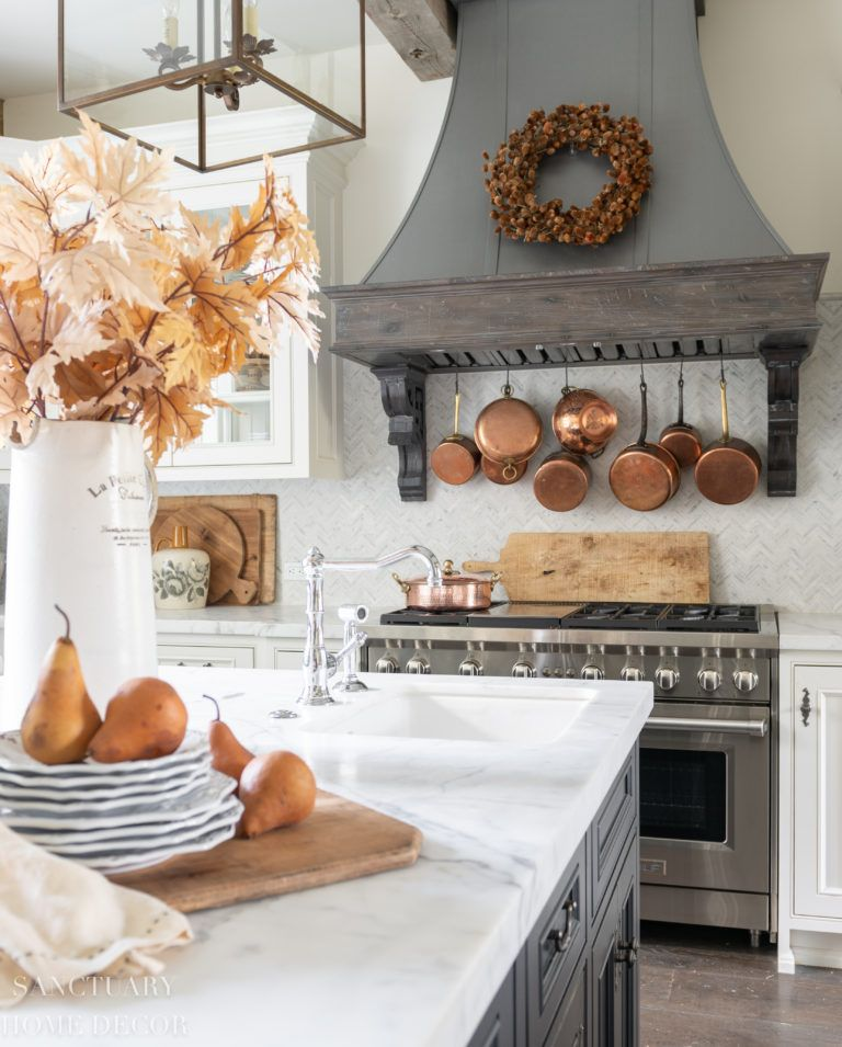 kitchen counter with fall leaves and pears on white plates