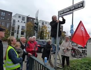 Am Straßenschild: Demonstranten mit DKP-Fahne. Uwe Koopmann montiert das Zusatzschild.
