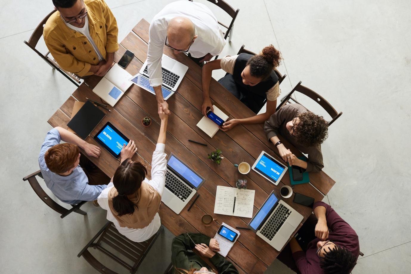 A group of people sitting around a table with laptops  Description automatically generated with medium confidence
