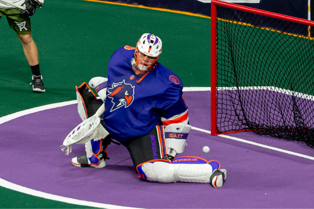 Image of a goalie tracking the rebound as it bounces off of his pads