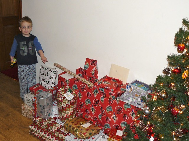 Child with many christmas gifts and a christmas tree