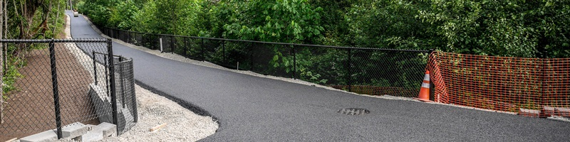 A photo of an asphalt multi-use trail surrounded by chainlink fence.