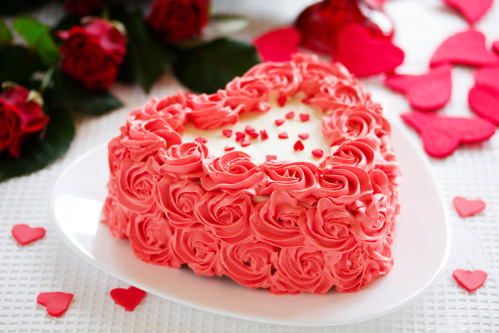 A heart-shaped cake decorated with pink roses made of frosting.