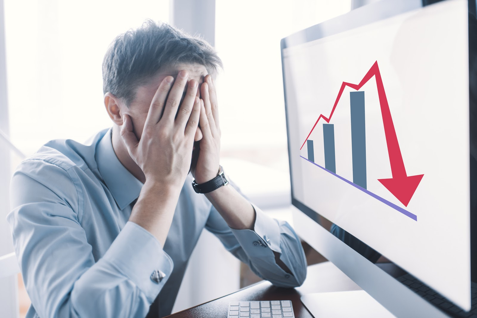 A man looking stressed at a downward trending graph on the computer
