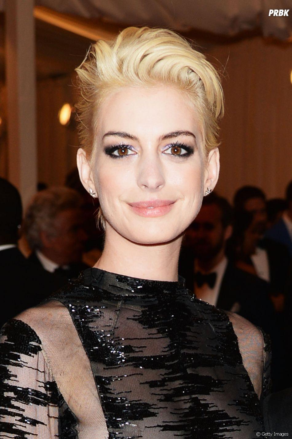Mulher branca possui cabelos loiros claros, maquiagem escura e veste vestido preto com transparências. Post Coloração Pessoal. Foto: Getty Images.