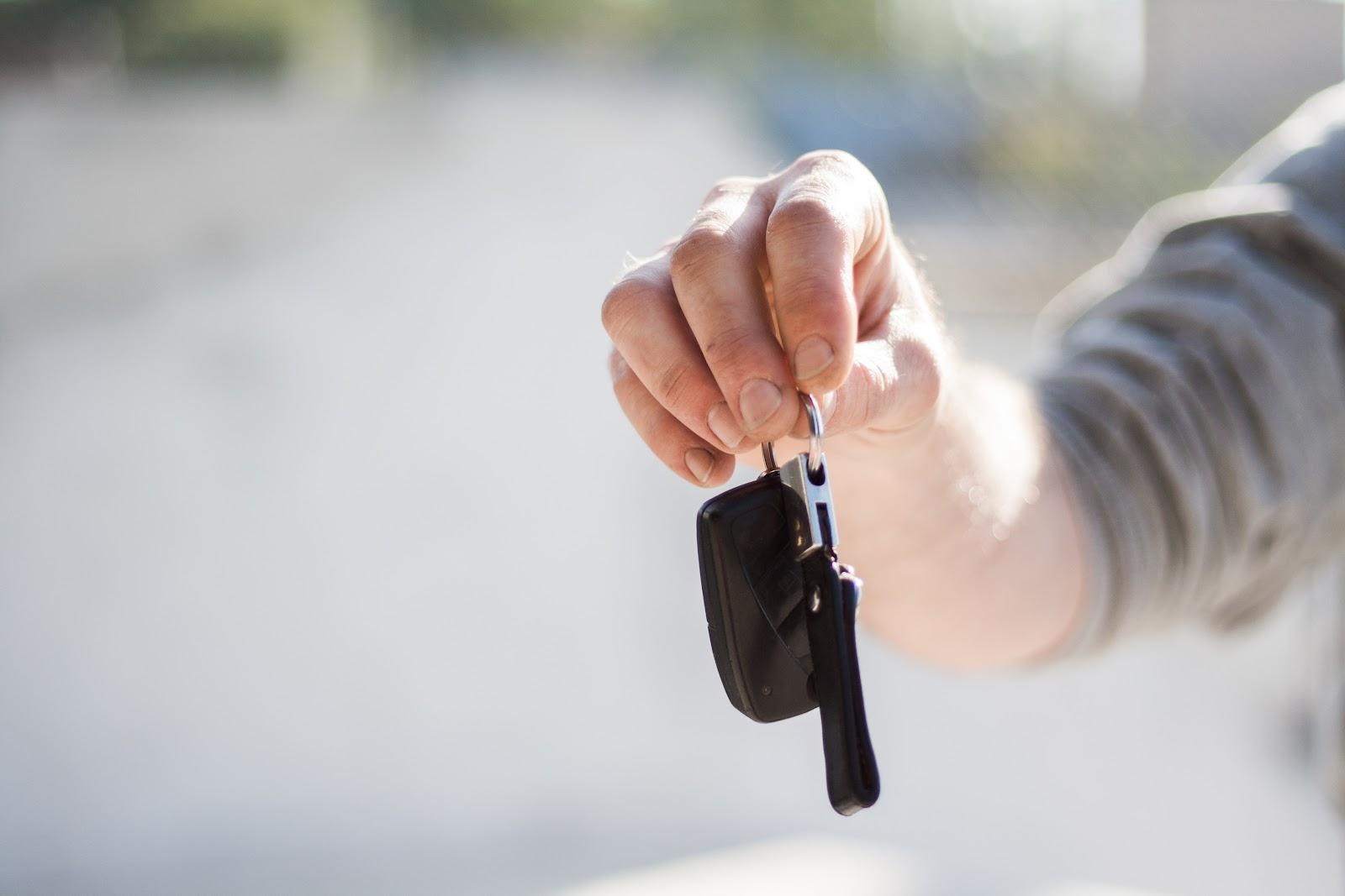 Mão segurando uma chave de um carro alugado para uber e 99.