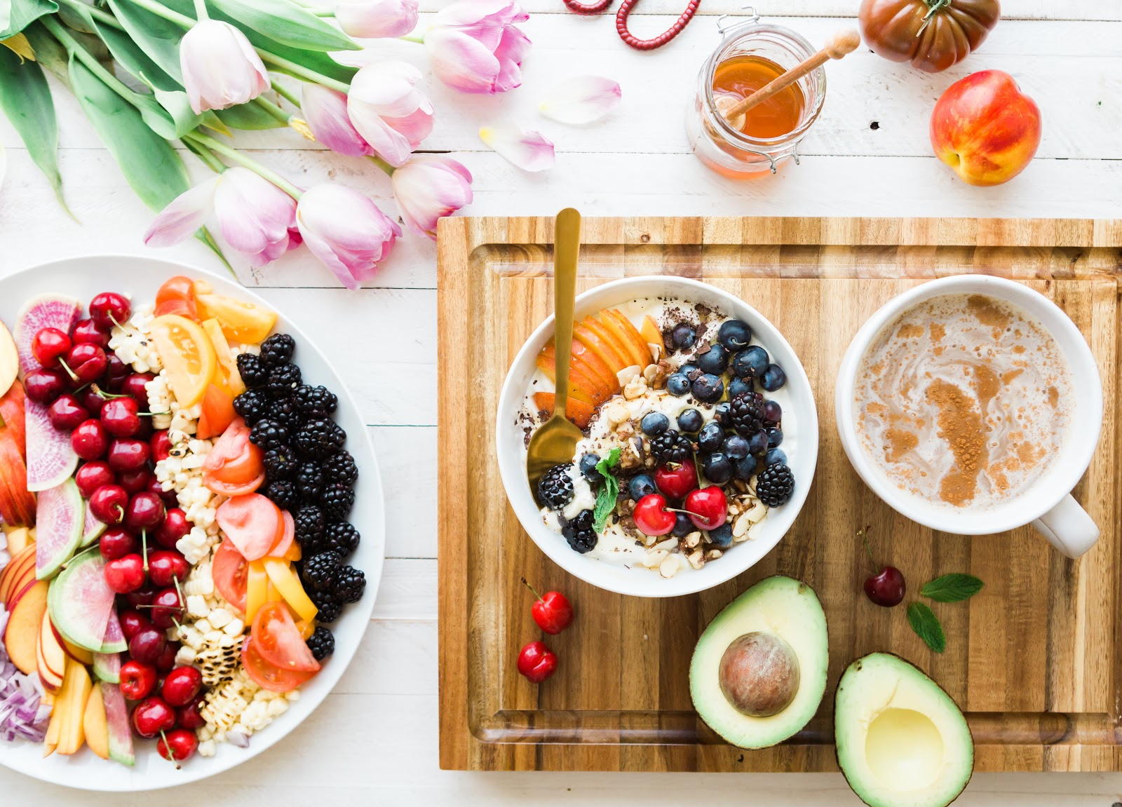 Top down view of an assortment of healthy foods on a cutting board and in a bowl.