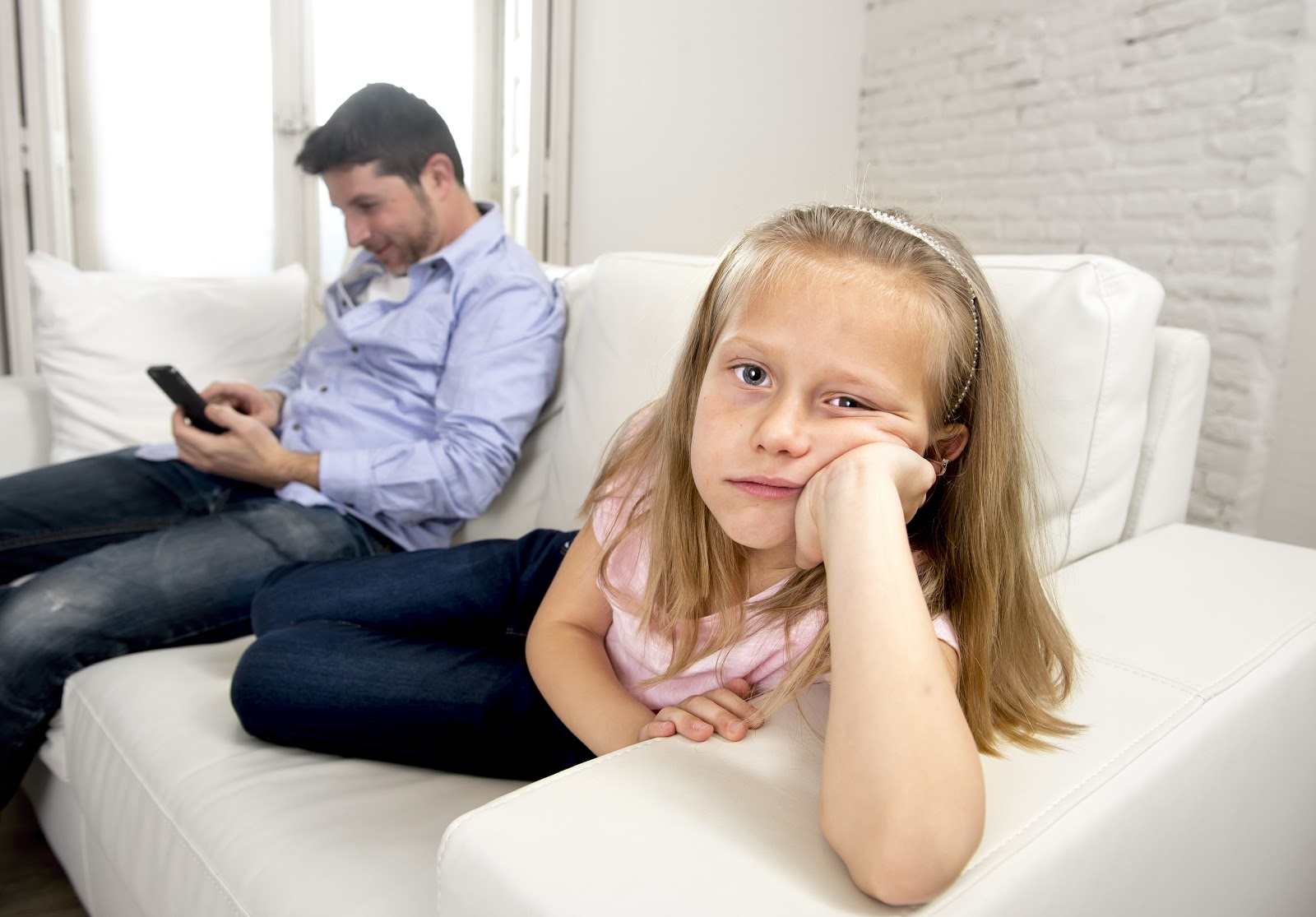 A young girl looking at the camera bored while her dad looks at his cell phone