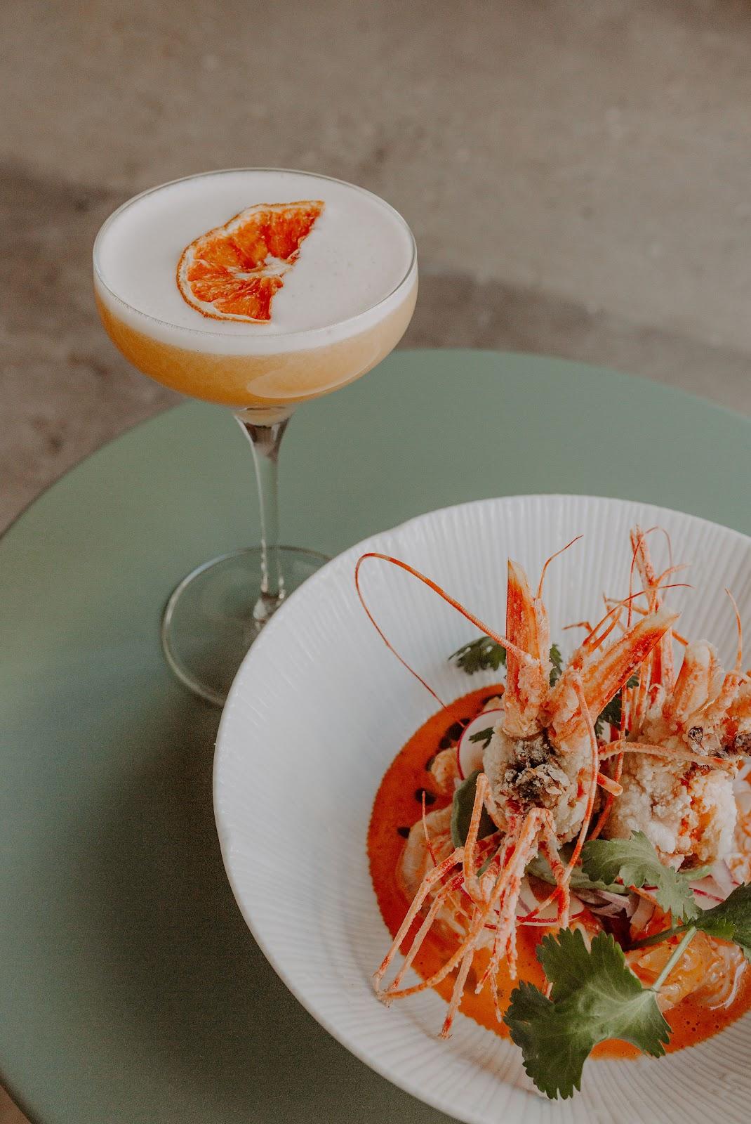 Grapefruit margarita next to plate of shrimp