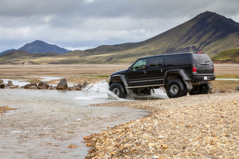 A black car driving through a river