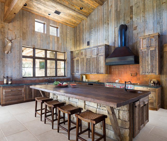 large cabin kitchen with wood accents and oversized island with butcher block and stone siding