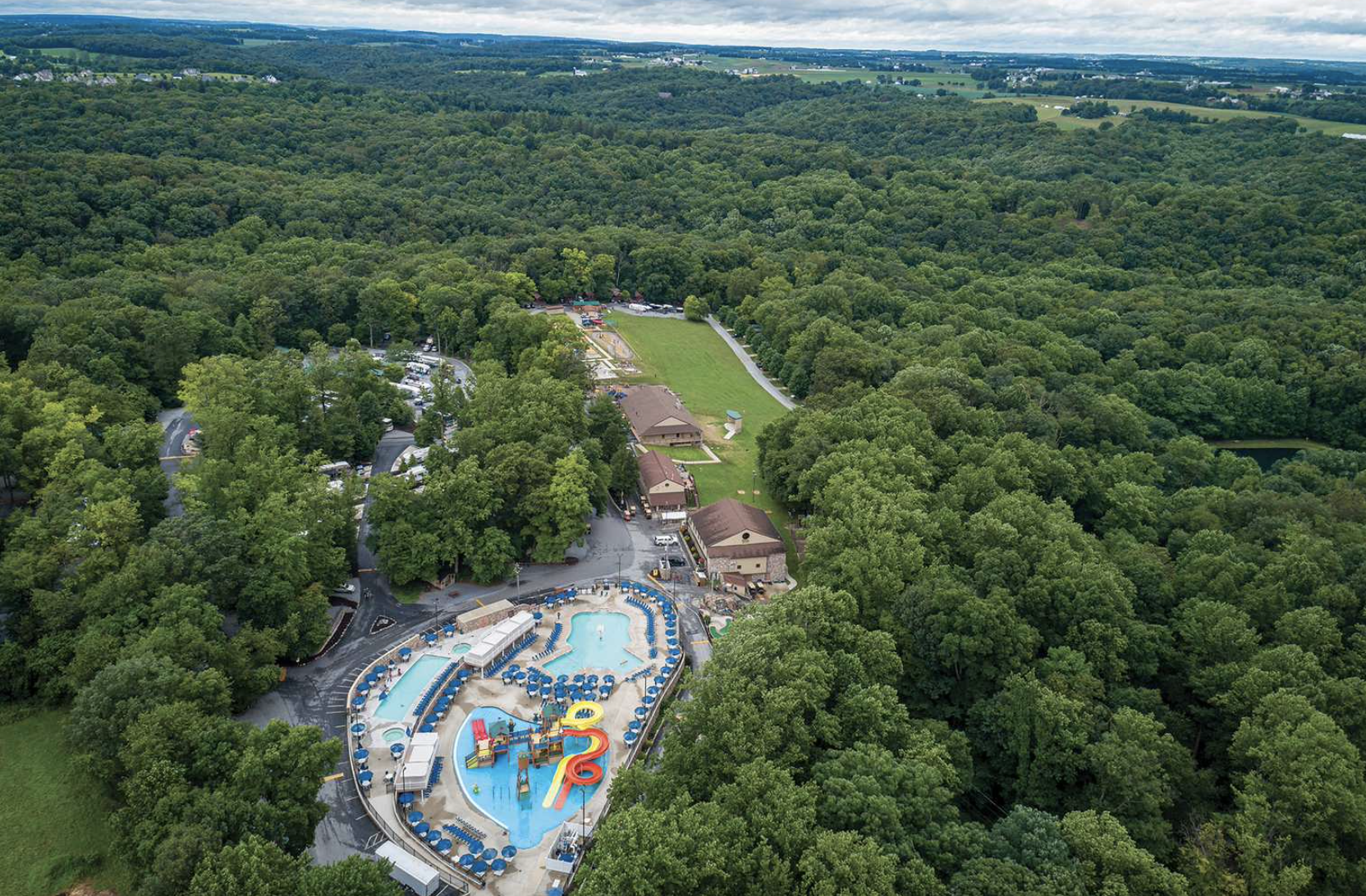 Aerial view of campground between lush woods with pool and water slide