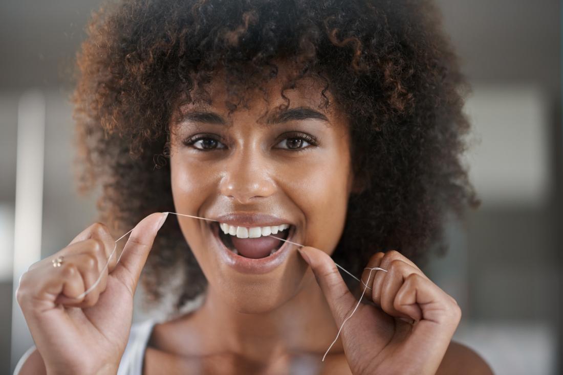 dişlerini diş ipi ile temizleyen kadın