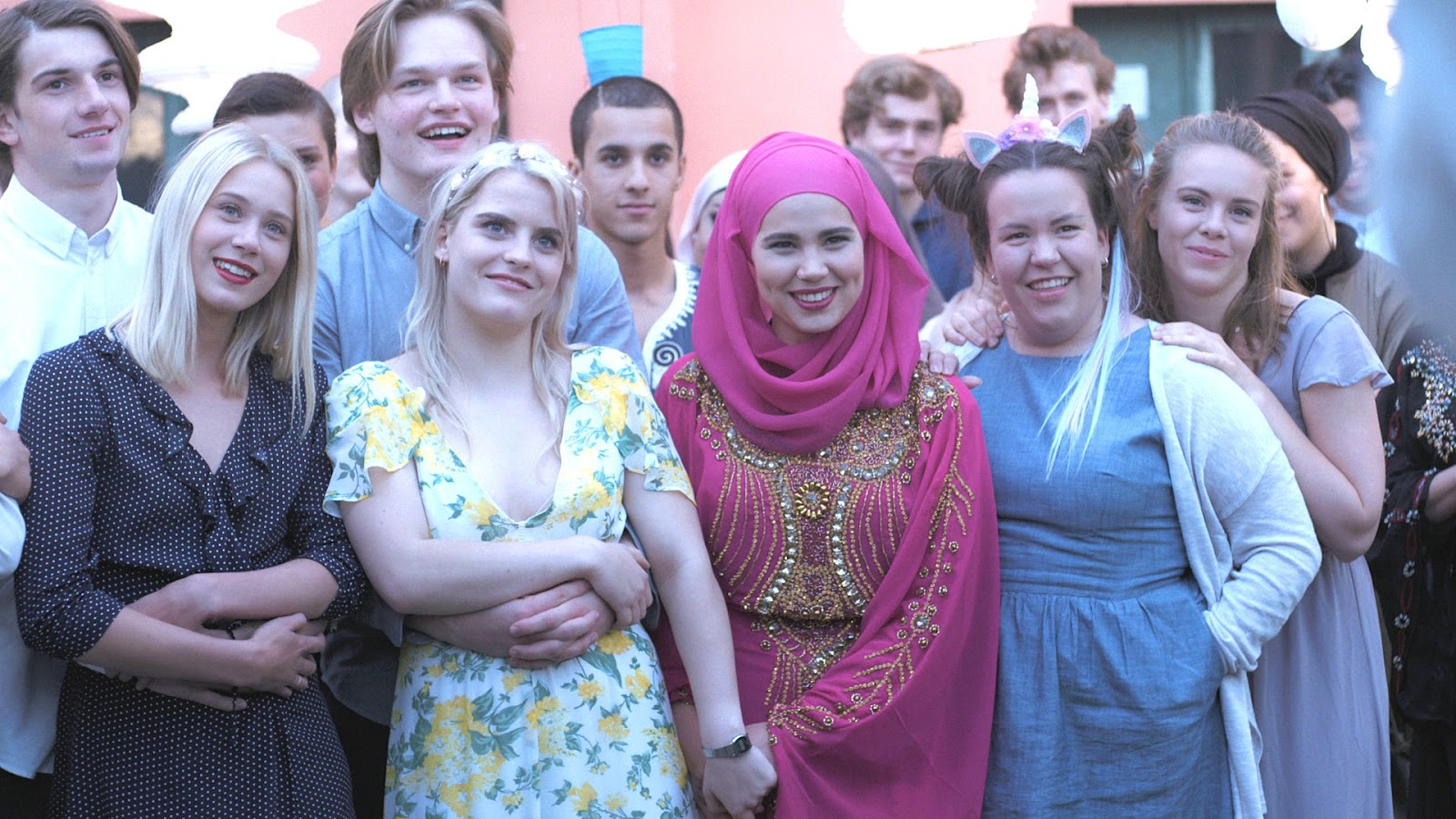 SKAM Norway. The five friends, Noora, Vilde, Sana, Chris, and Eva, are all dressed up at a party, standing in a crowd with boys behind them. They are all looking up and smiling, Vilde and Sana are holding hands. Eva has her hands on Chris' shoulders.