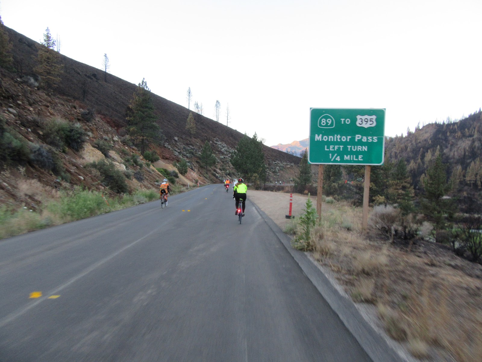 Cycling Monitor Pass West - beginning of climb - Death Ride - cyclists and Monitor East and West road sign