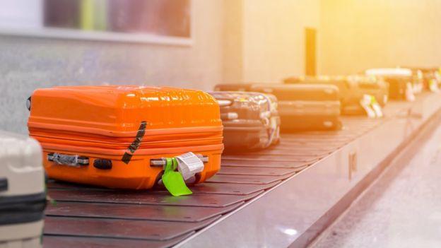 Оранжевый чемодан на ленте