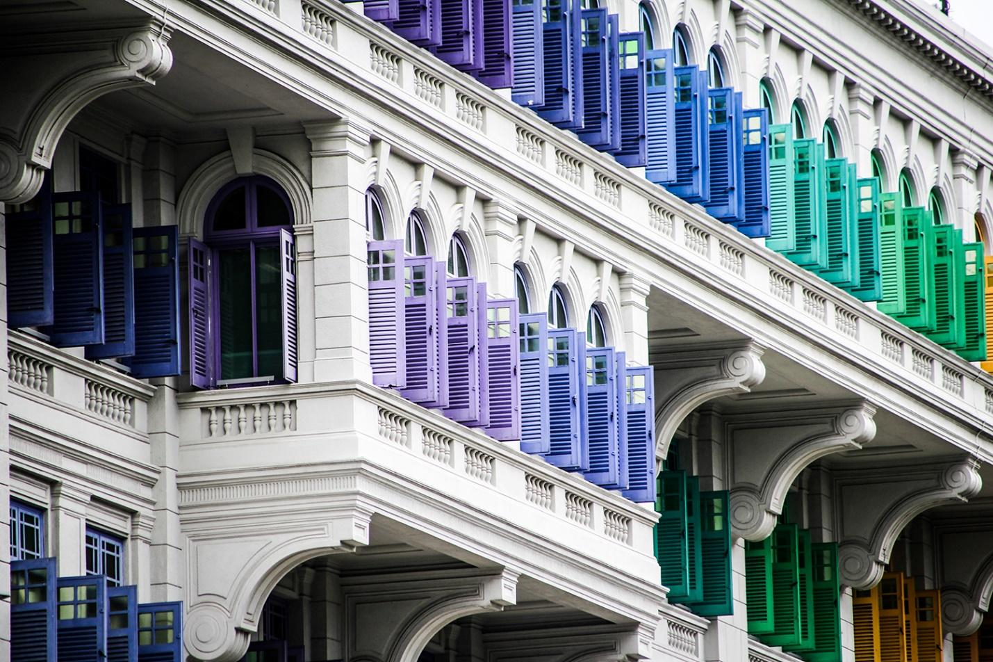 Colorful window shutters on a multistory building creating a rainbow effect.