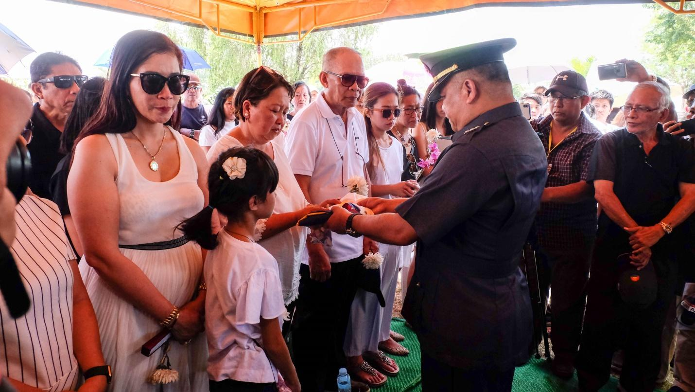 APOLOGIES. Colonel Claro Unson, PMA Deputy Dean of Academics hands the Philippine flag to Jazy Dormitorio, Darwin's mother, as husband retired Army Colonel William Dormitorio looks on. Photo by Bobby Lagsa/Rappler