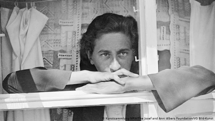 Anni Albers, a black and white photo of her shown looking out her window, one of our featured women in design.