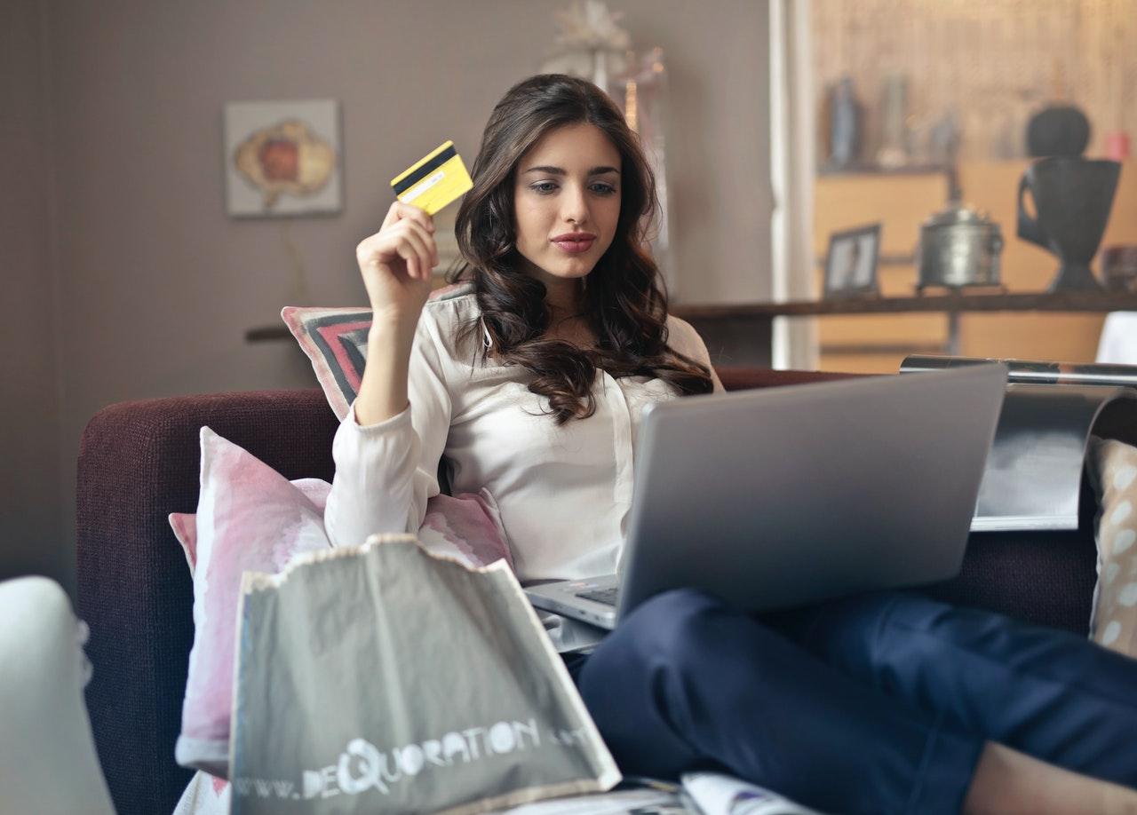 Siedząca w pokoju kobieta z laptopem, kartą kredytową i torbami z zakupami obok siebie