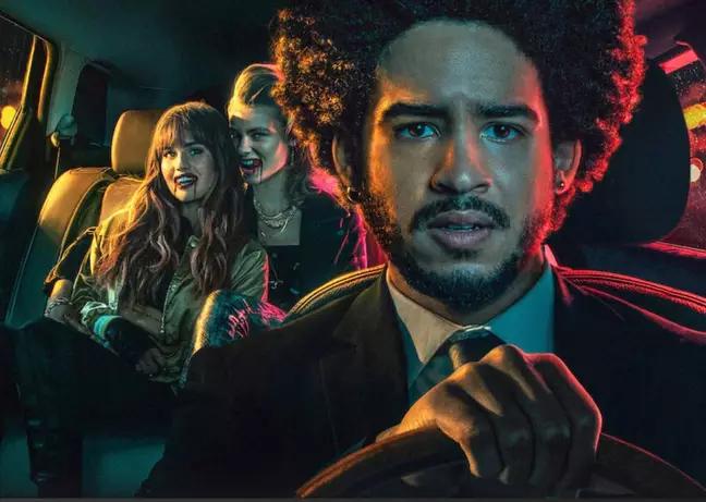 Homem preto com black power veste terno e é motorista de um carro com duas passageiras mulheres brancas no banco de trás. Filme As passageiras. Foto: Divulgação Netflix.