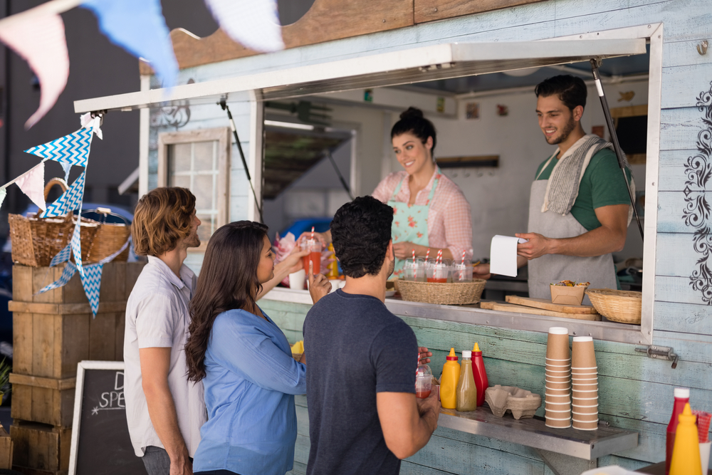 A group of people purchasing food from a food truck.