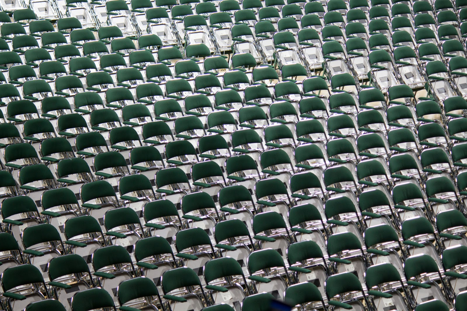 Rows of empty green chairs from a sports stadium