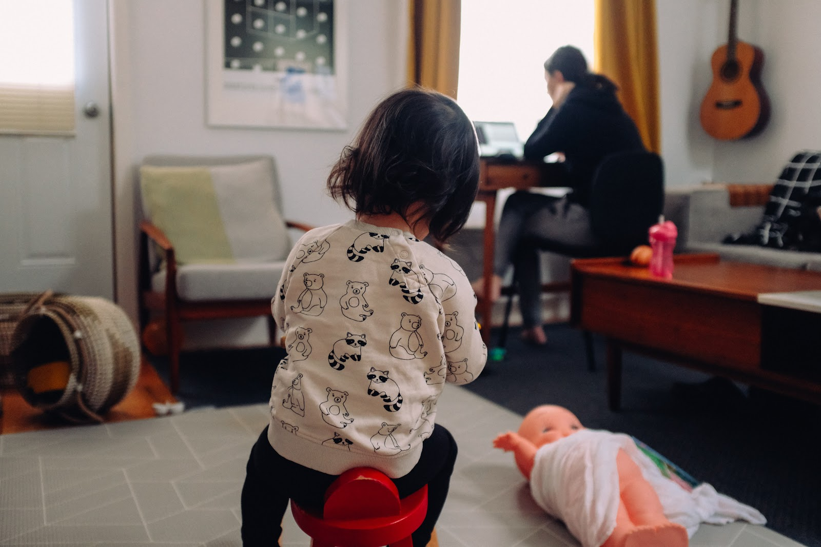 Work from home set up with child and toys in the foreground while parent works in the background; Thanks to Charles Deluvio for sharing their work on Unsplash.