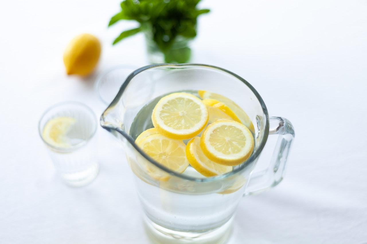 A water jug full of lemon-infused water against a white background