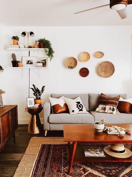 Sala com estilo rústico, sofá cinza com almofadas brancas e marrons, móveis e acessórios de madeira.