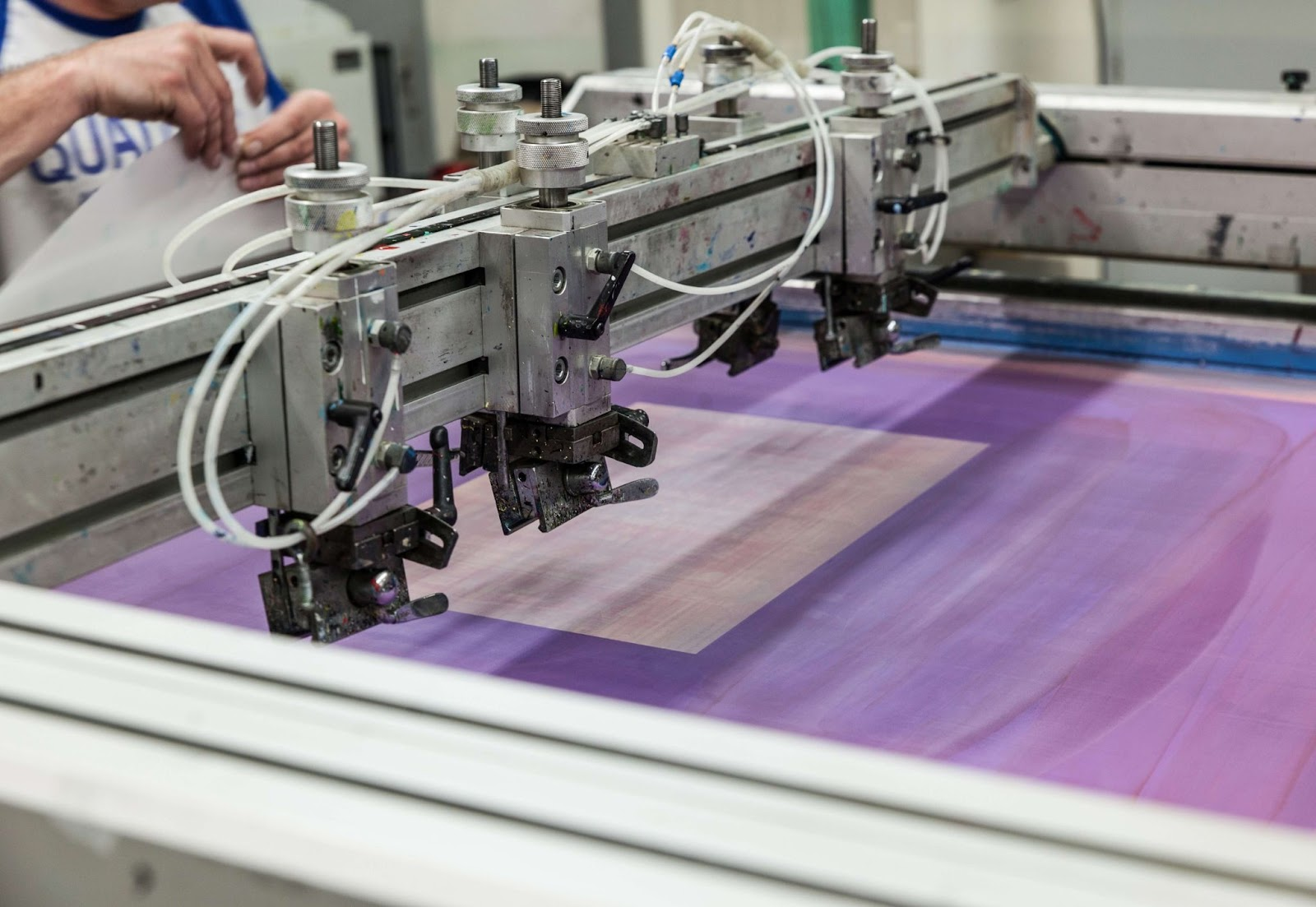 Man operating printing machine and monitoring for quality control