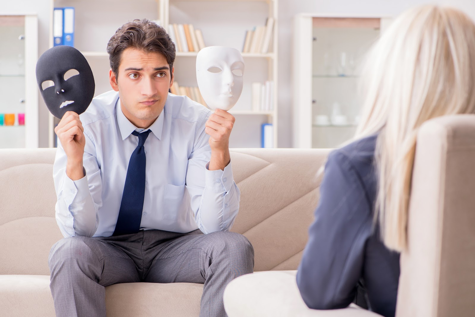 A man in therapy holding two masks, trying to deal with a crisis