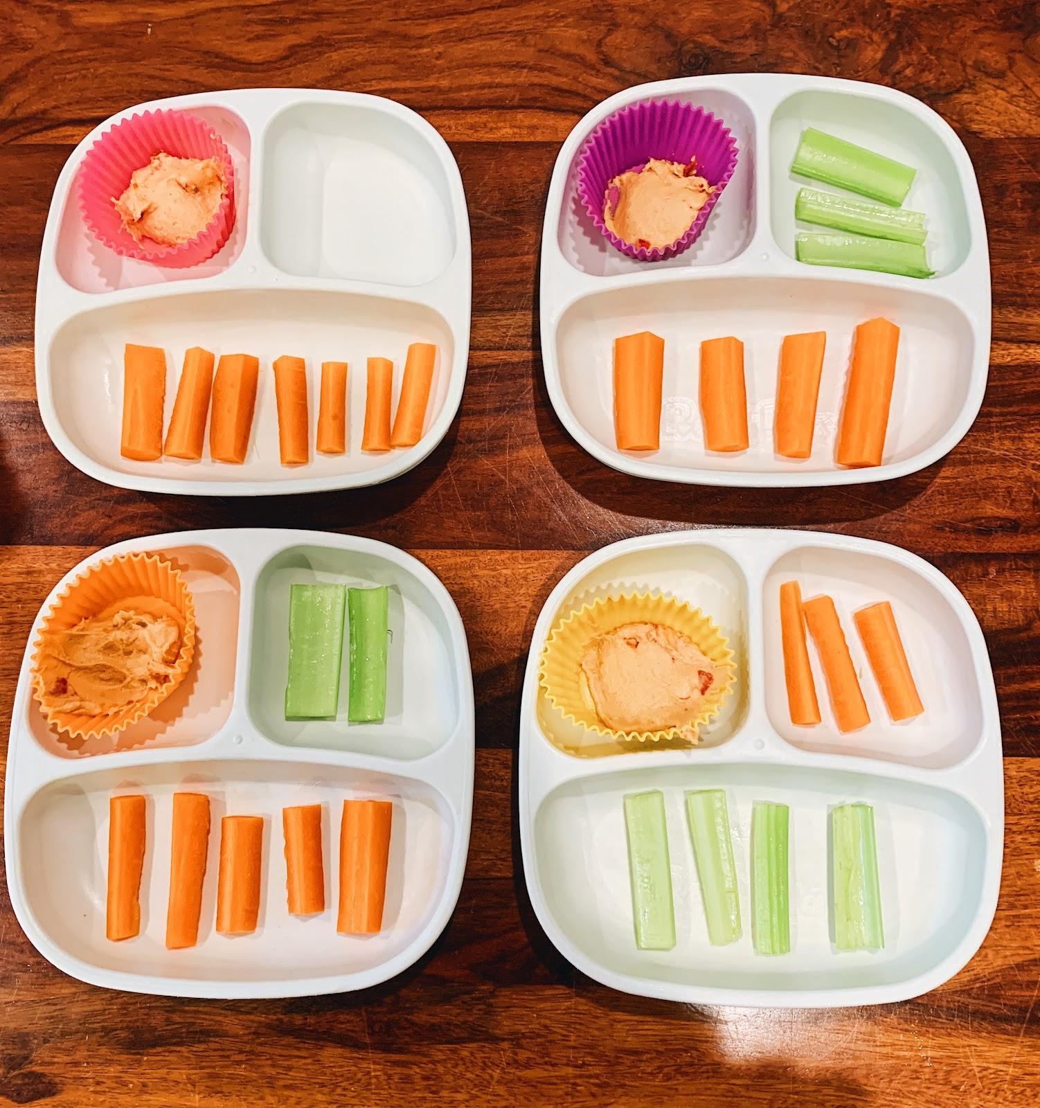 One snack tray has hummus and 7 carrots. No celery. Another tray has hummus, 4 carrots, and 3 celery sticks. A third snack tray has hummus, 5 carrots, and 2 celery sticks. The last tray has hummus, 3 carrots and 4 celery sticks.