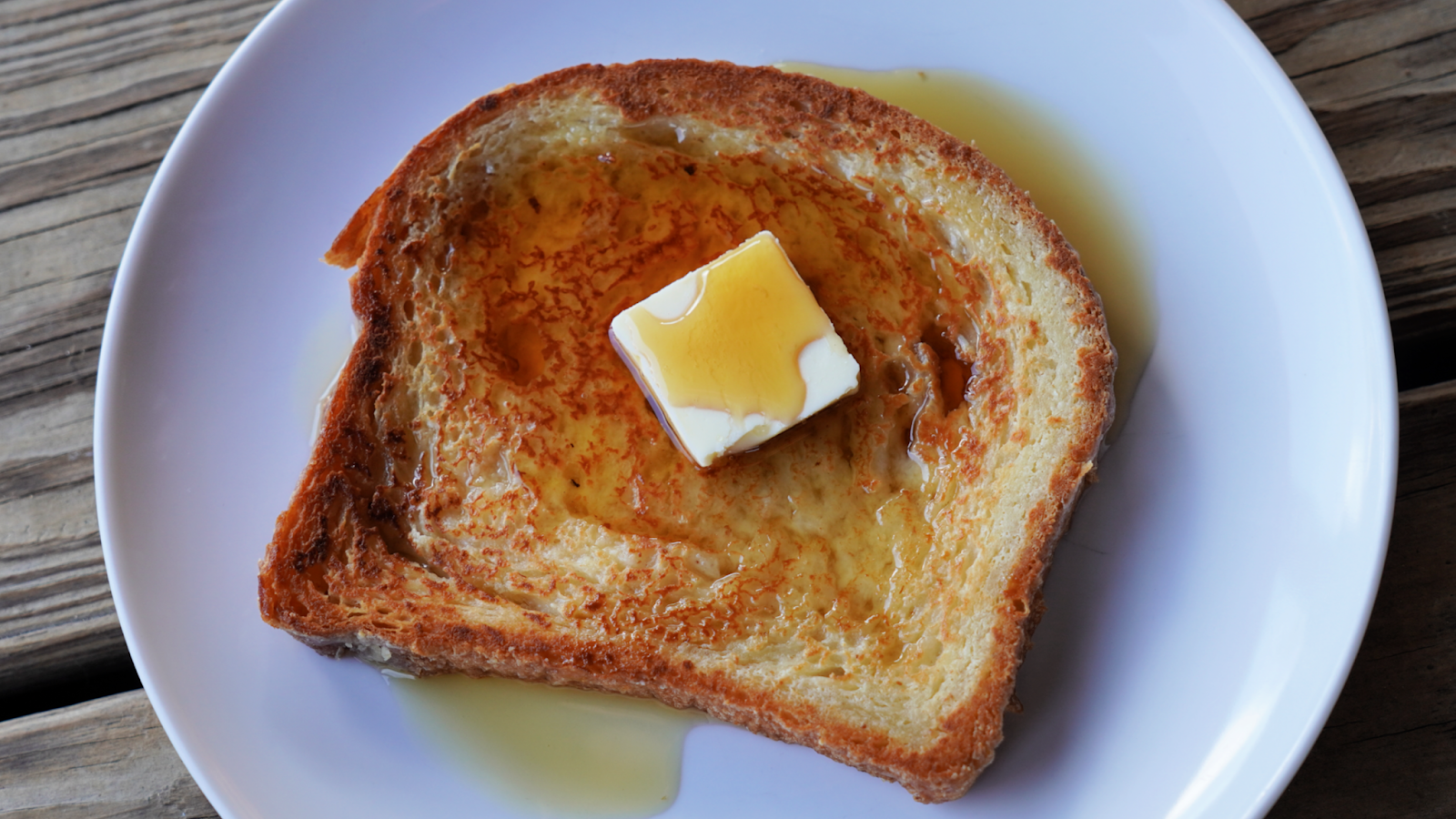 A slice of french toast topped with a pat of butter and maple syrup on a white plate and wood background.