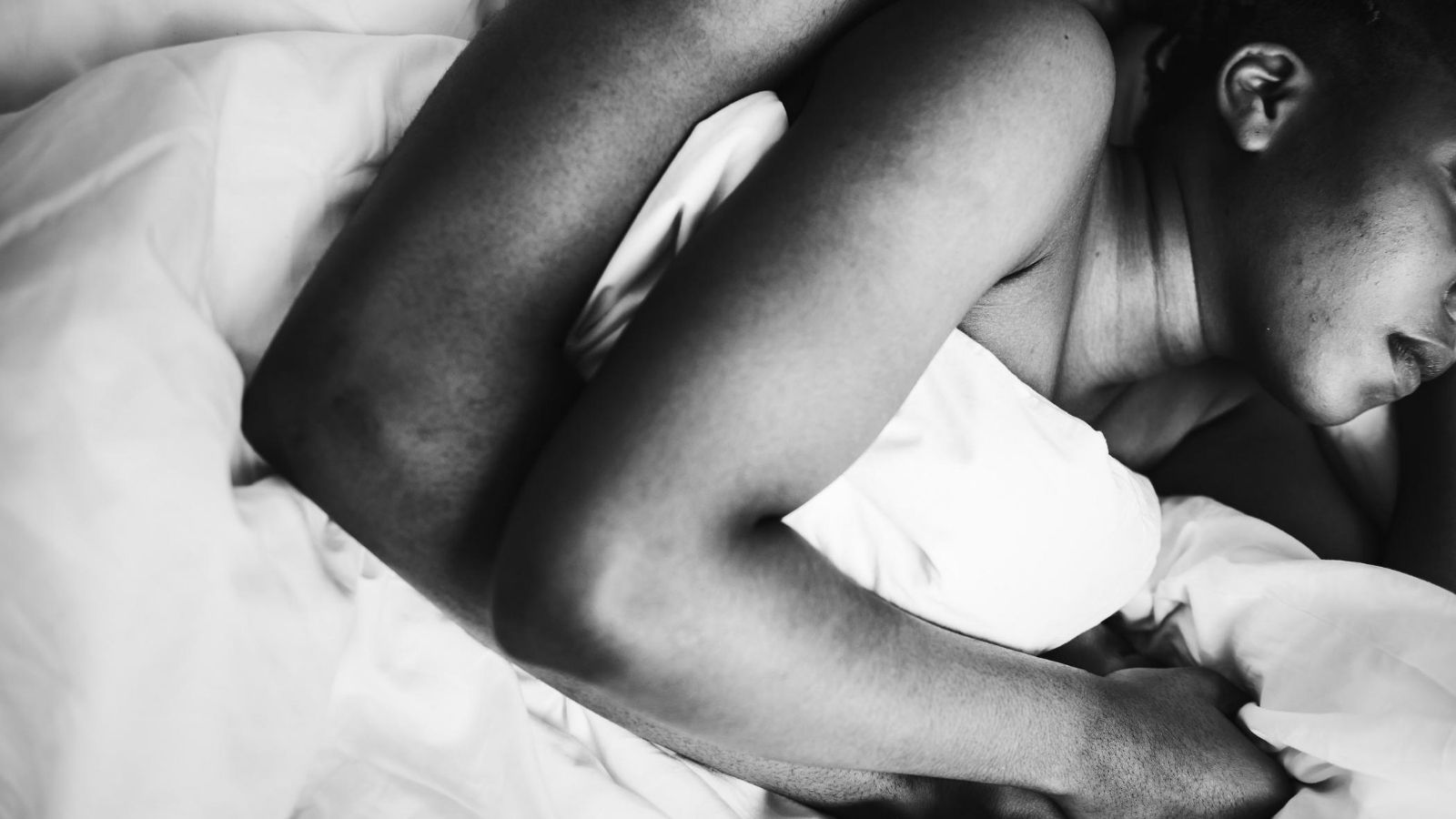 A black and white image of a couple in bed
